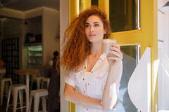 Cute redhead woman with long hair holding cup of coffee Royalty Free Stock Image