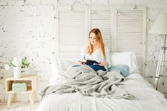 Cute Redhead Woman Reading Book at Home. Girl with Grey Woolen Blanket Stock Image
