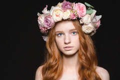 Cute redhead woman with wreath from flowers on head. Beauty portrait of a cute redhead woman with wreath from flowers on head standing over black background Royalty Free Stock Photos