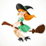 Cute redheaded witch in green dress flying on a broom Stock Photo