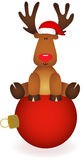 Cute reindeer sitting on Christmas ball Stock Images
