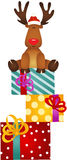 Cute reindeer sitting on Christmas Gifts Royalty Free Stock Image