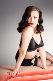 Cute retro pinup in black lingerie on vintage chaise Royalty Free Stock Photos