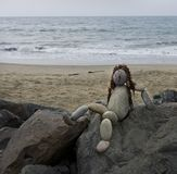 Cute rock art statue of a lady at the beach. Hair made of kelp. She is in a relaxed position. Beach and ocean in the background Stock Image