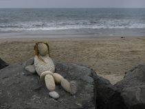 Cute rock art statue of a lady at the beach. Hair made of kelp. She is in a relaxed position. Beach and ocean in the background Stock Images