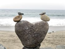 Cute rock art statue of two ducks at the beach. Beach and ocean in the background Royalty Free Stock Photos