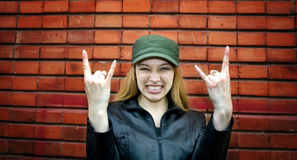 Cute rocker girl. With old brick wall as background Stock Photography