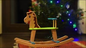 Cute rocking horse chair - good gift for Christmas or New year for the baby from Santa Claus or parents. Cute rocking horse chair for children stand near stock video footage