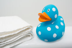 Cute Rubber Duck beside White Towel in Bathroom Close Up Stock Images