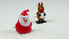 Cute Rudolph the red-nodes reindeer windup dolly walks next to a winking Santa Claus stock video