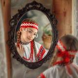 Cute Russian girl in folk costume looks in the mirror