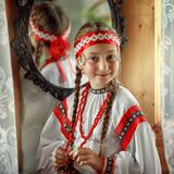 Cute Russian girl in a traditional costume on the background of a mirror
