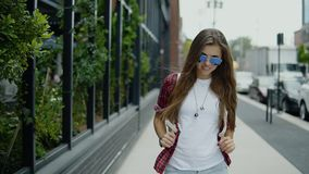 Attractive young woman in sunglasses and trendy clothes checking time on her watch walks near street cafe. Cute 30s girl with long brown hair dressed in fashion stock video footage