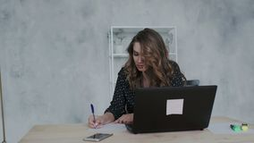Young natural curly self confident brunette girl in black dress working at home using laptop. Remote work in coworking. Cute 20s lady working at desk in trendy stock video footage