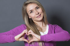 Cute 20s woman showing heart shape with hands Stock Image