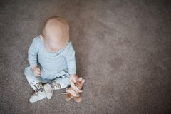 Cute sad baby girl with little bunny in hand. Close up portrait of little girl with toy in grey dress. Cute sad baby girl with little bunny in hand. Close up Royalty Free Stock Images