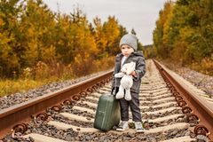 Cute sad boy in retro clothes with a vintage green suitcase standing on rails in the forest Royalty Free Stock Image