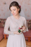 Cute sad bride at home in white wedding dress, preparations concept. Portrait of tender depressed girl in gown.  Royalty Free Stock Photos
