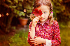 Cute sad child girl hiding behind red autumn leaf in the garden Royalty Free Stock Photos