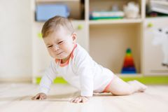 Cute sad crying baby on ground in kids room. New born child, little girl looking at the camera and crawling. Family, new life, childhood, beginning concept royalty free stock photo