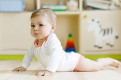 Cute sad crying baby on ground in kids room. New born child, little girl looking at the camera and crawling. Family, new life, childhood, beginning concept stock photo