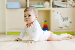 Cute sad crying baby on ground in kids room. New born child, little girl looking at the camera and crawling. Family, new. Life, childhood, beginning concept royalty free stock images
