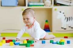 Cute sad crying baby playing with colorful wooden blocks toys stock photo