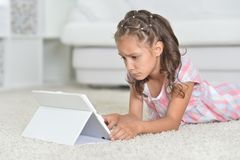 Portrait of cute sad girl with digital tablet on floor royalty free stock images