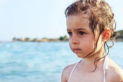 Cute Sad Little girl is looking at the wide sea at summer Royalty Free Stock Images