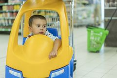Cute sad little 2 year old baby boy child in the little toy-car trolley at supermarket, Dad or Parent pushing child shopping cart stock photography