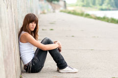 Cute sad teenage girl sitting. Alone in urban environment Royalty Free Stock Images