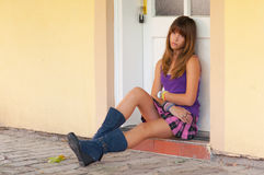 Cute sad teenage girl sitting in front of the door. Cute sad teenage girl sitting in front of the white door Stock Image