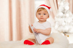 Cute santa baby with tablet. Cute santa baby holds tablet Royalty Free Stock Photos