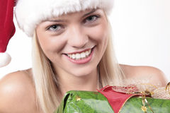 Cute Santa Blond Girl. Closeup Portrait Of A Cute Blond Girl With Christmas Present Royalty Free Stock Image
