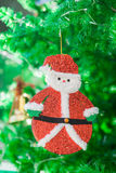 Cute Santa claus doll and gold bell ornament on Christmas Tree. Cute Santa claus doll and gold bell ornament on green Christmas Tree Stock Photos