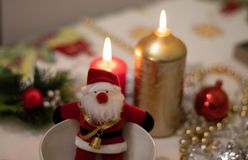 Santa Claus doll inside a bowl with on a Christmas tablecloth with candles royalty free stock photography