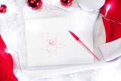 Cute Santa drawn by a child with a red pen and a white sheet of paper and around are red Christmas balls and lights garland.