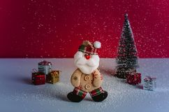 Cute Santa felt doll between a gifts pile and a Christmas tree while snowing. Red background and beautiful light. Royalty Free Stock Photos