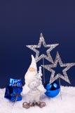 Cute santa figure on blue background. Santa ceramic toy with xmas balls on blue background Stock Images