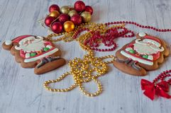 Cute Santa figures made of glazed honey cookies laying near red bow knot, golden beads and decorative balls on light wooden backgr. Two cute Santa figures made royalty free stock photos