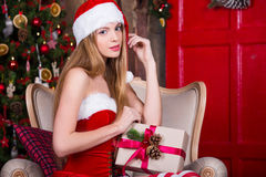 Cute Santa girl dreaming near the Christmas tree, making a wish. Vintage new year atmosphere. Xmas dreams Stock Image