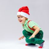 Cute santa's helper squats on white Royalty Free Stock Photos