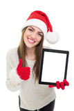 Cute Santa young woman showing tablet computer and thumb up Royalty Free Stock Image