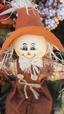 Cute scarecrow doll with large orange hat smiling Royalty Free Stock Image
