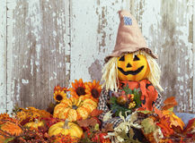 Cute scarecrow surrounded by autumn decorations Stock Photo