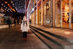 Cute scared lost little girl in a big city in the evening in winter stock photo