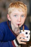 Cute school boy drinks milkshake Royalty Free Stock Image