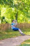 Cute school boy enjoying swing ride on playground. Cute school boy enjoying a swing ride on a playground on a hot summer day Royalty Free Stock Photo