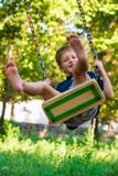 Cute school boy enjoying a swing ride. On a playground on a hot sunny summer day Stock Photos