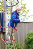 Cute school boy having fun outdoors at playground Stock Images